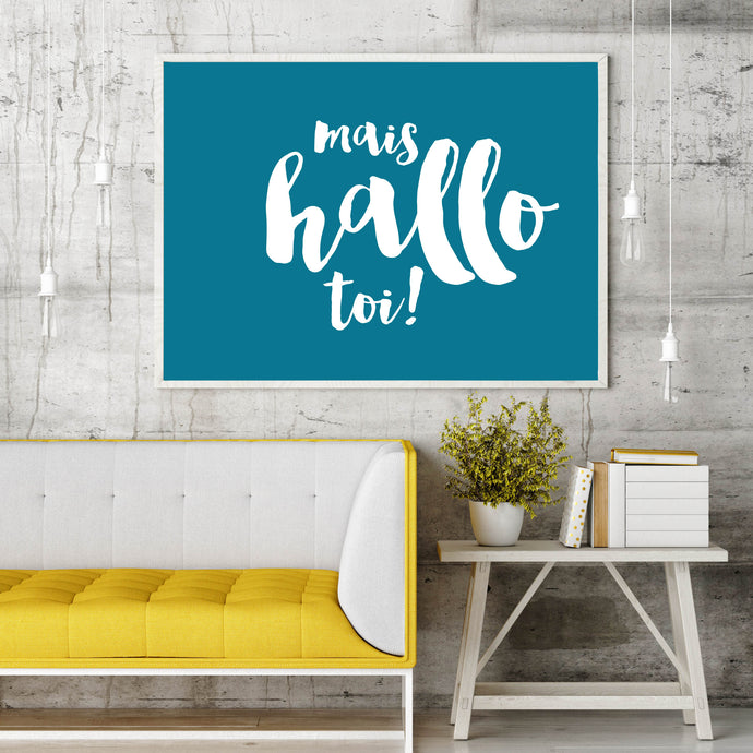 A large French Acadian/Acadien saying (mais hello toi!) printing and framed above a bright yellow couch.