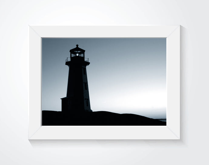 Framed lighthouse photograph hung on a white wall.