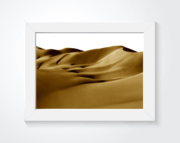 Framed photo of sand dunes hung on a white wall.