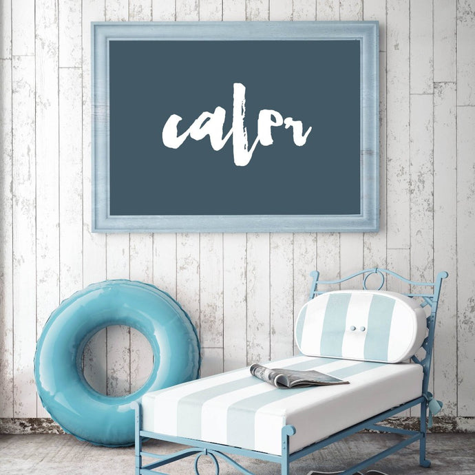 A french Acadian framed art print on a wall with a chair and swimming floater beside it.