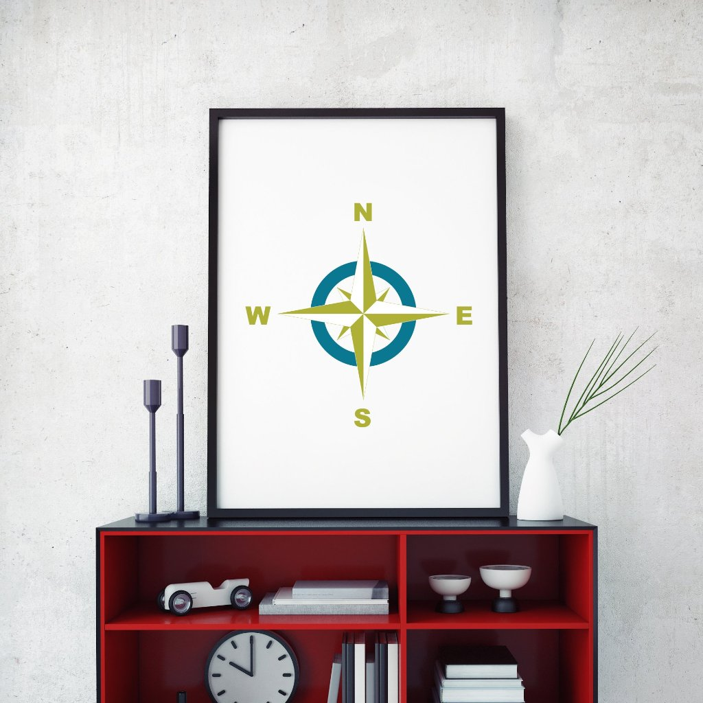 A compass rose art design framed on a table.