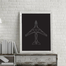 A modern geometric illustration of an aircraft printed and framed on a modern desk with a lamp hanging near.