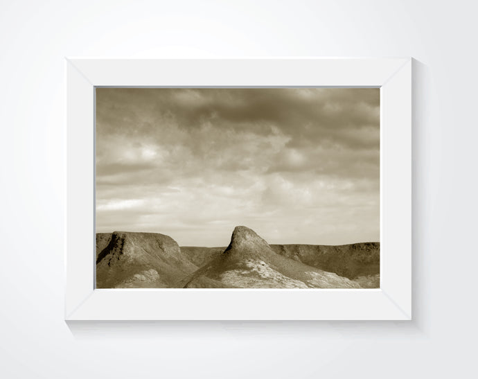 A photograph of a desert in sepia tones framed and on a white wall.