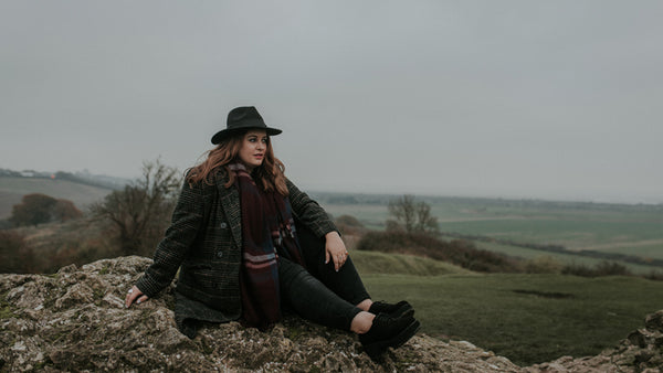 Jenna sat on castle ruins with fedora hat