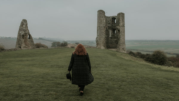Jenna walks off into the distance surrounded by castle ruins