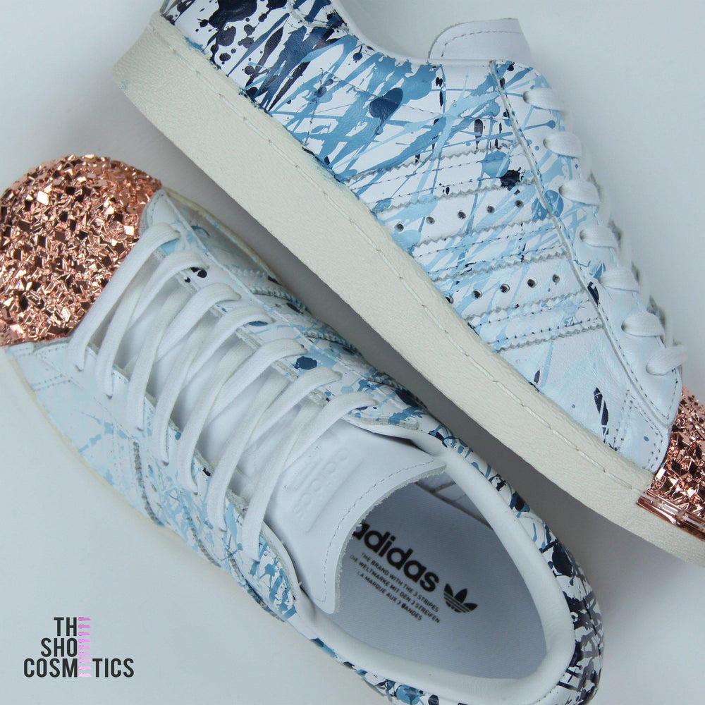 7c6e3818db9 TheShoeCosmetics - Blue Splatter Adidas Superstar Rose Gold Shell Toe  Custom Shoes