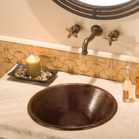 a small oval copper sink in a bathroom