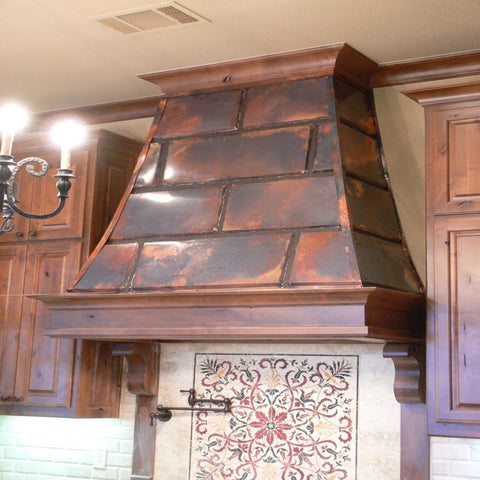 small hand hammered copper range hood in a kitchen