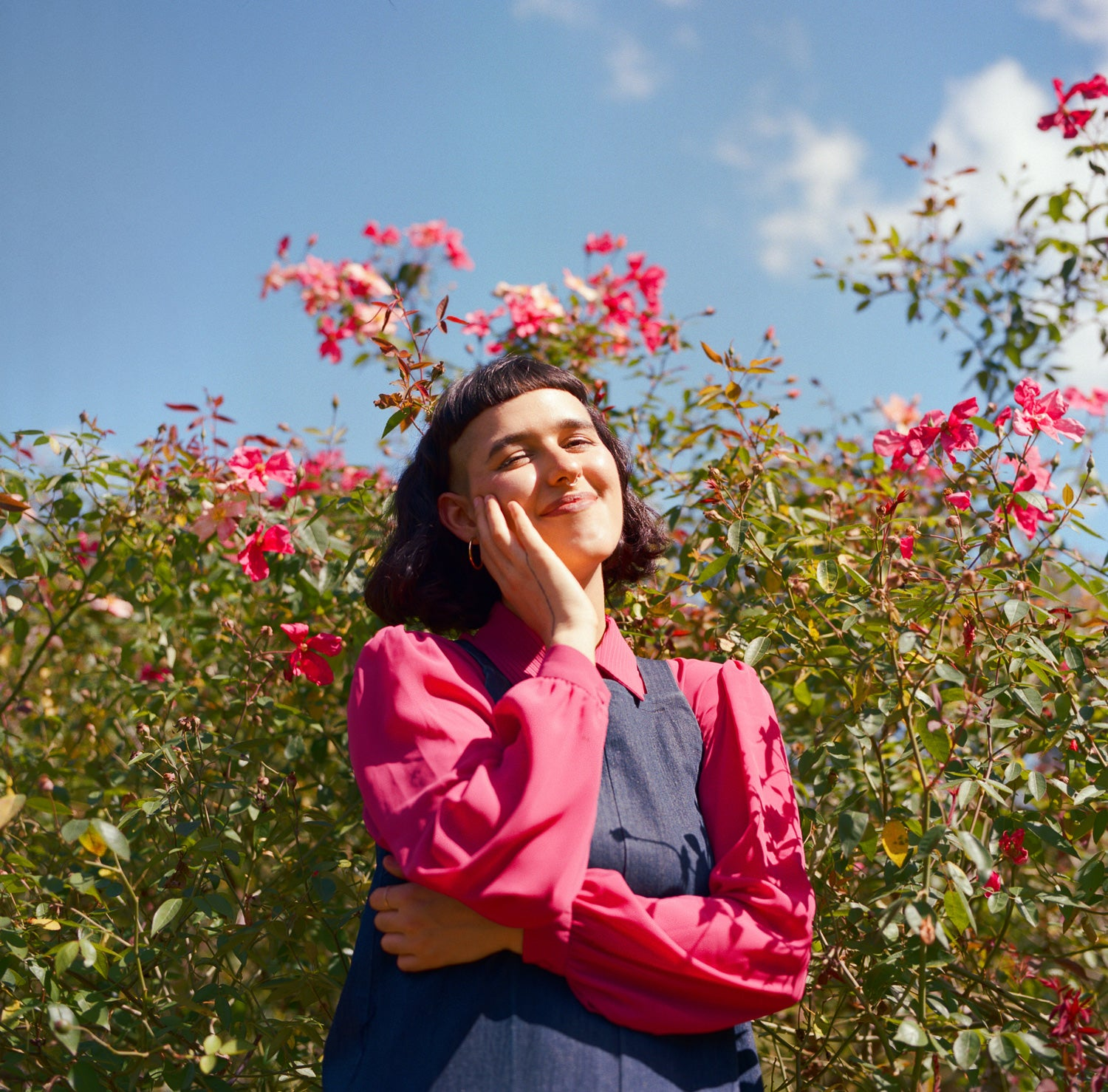 Film portrait of Christine. She is standing in front of a pink flowering bush, with her hand to the side of her face in a warm moment.