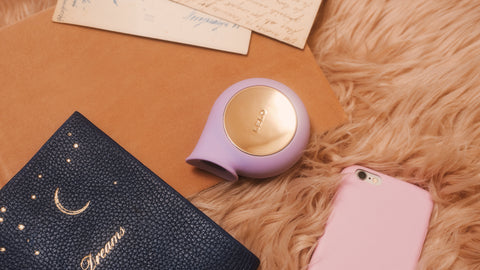 Lelo Sila Clitoral Vibrator lays on its side in the shade of soft Lavender. The toy shines with warm metal details which complements the warm & inviting environment it creates. It lays atop a caramel furry rug, tan leather folder, and amongst a black celestial journey, baby pink phone case and love letters.