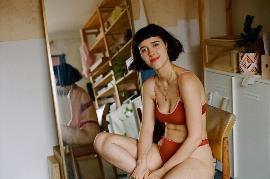 Film portrait of Christine sitting on a Mustard vinyl chair, in her studio