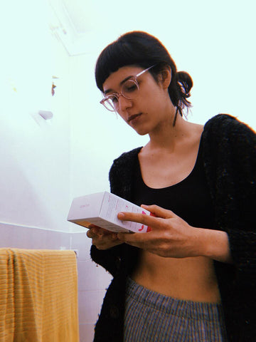Christine standing and reading the instructions on the Menstrual Cup box intensely.