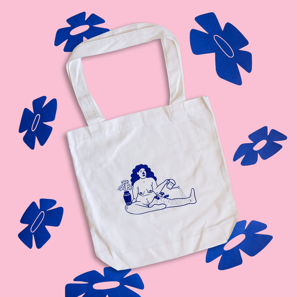 The 'Growing Tote Bag', captured from a flat lay point of view, on top of a mid-pink background. Around the tote are blue flowers that mimic the flowers in the artwork on the bag.