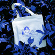 The 'Growing Tote Bag' sits amongst blue leaves & foliage, almost mimicking the blue tone of the illustration on the tote bag.