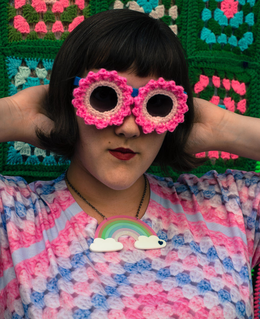 Ashley Zhong models a pair of crocheted sunglasses or funny sunnies in front of a wall of granny squares