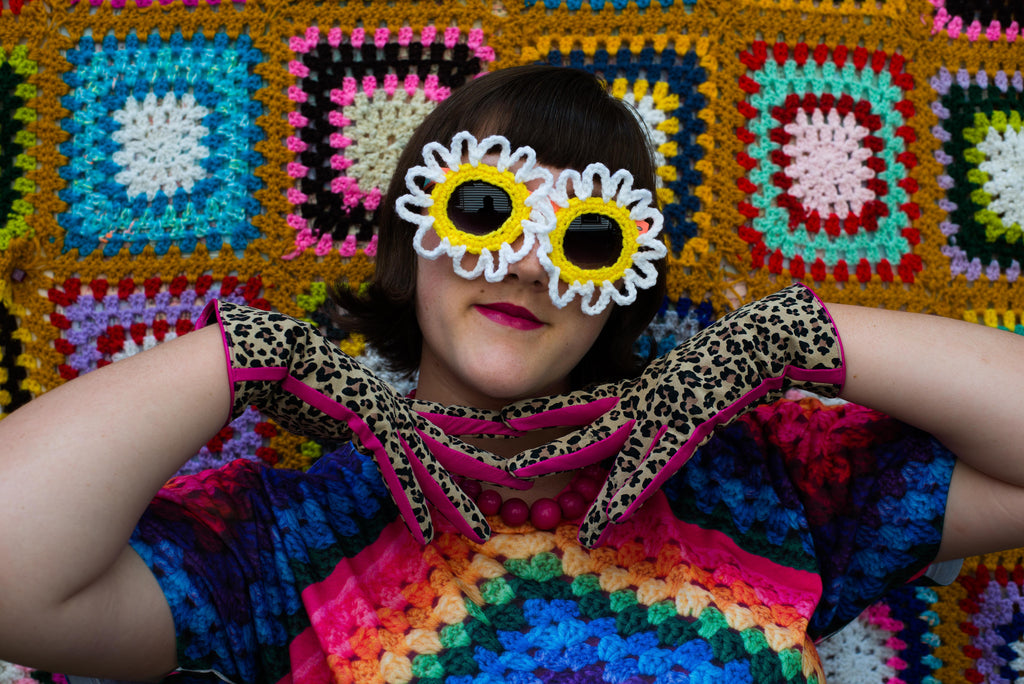 Ashley Zhong modeling crocheted sunglasses in front of a wall of granny squares