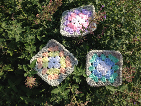 gray and pastel granny squares on a bed of purple flowers