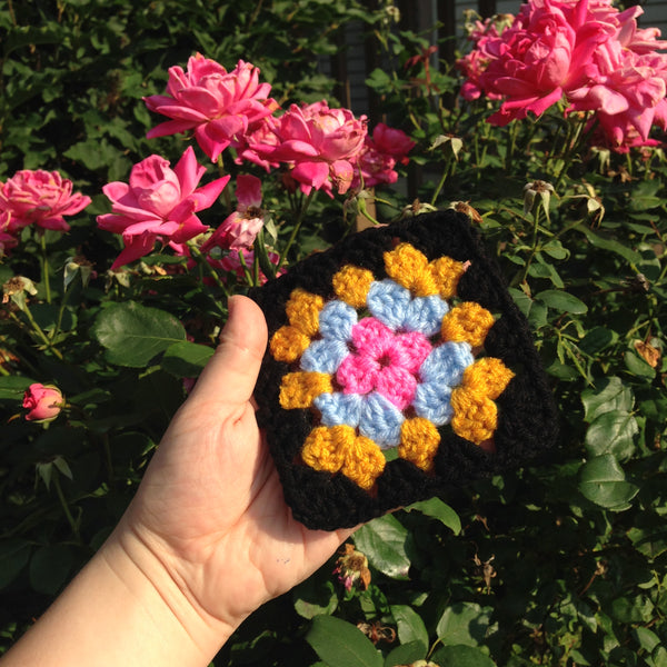 A classic granny square with a black border in front of a rose bush
