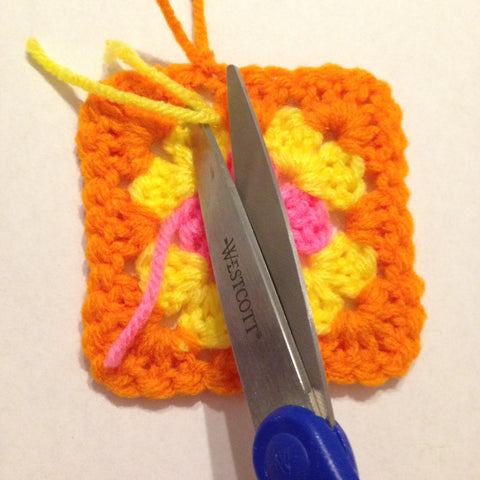 trimming the tails of yarn on a granny square