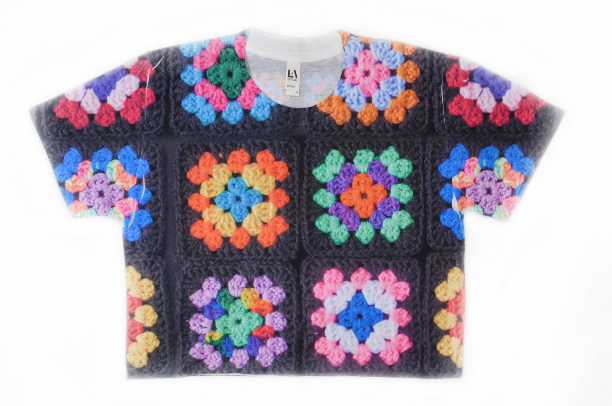 Snapdragon Brand Clothing Granny Square Crochet Print rainbow crop top cropped t-shirt in style Kaleidoscope features a vintage boho feel and a rainbow of colors. Made of comfortable polyester.