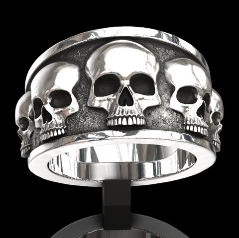 Five skull flared band ring.