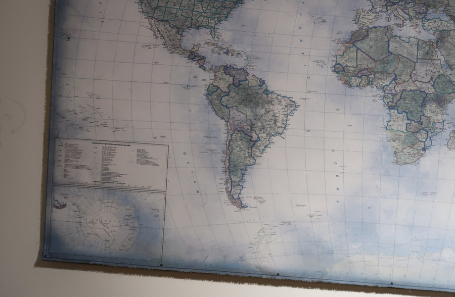 Wall art with dark edges and large blue world map.