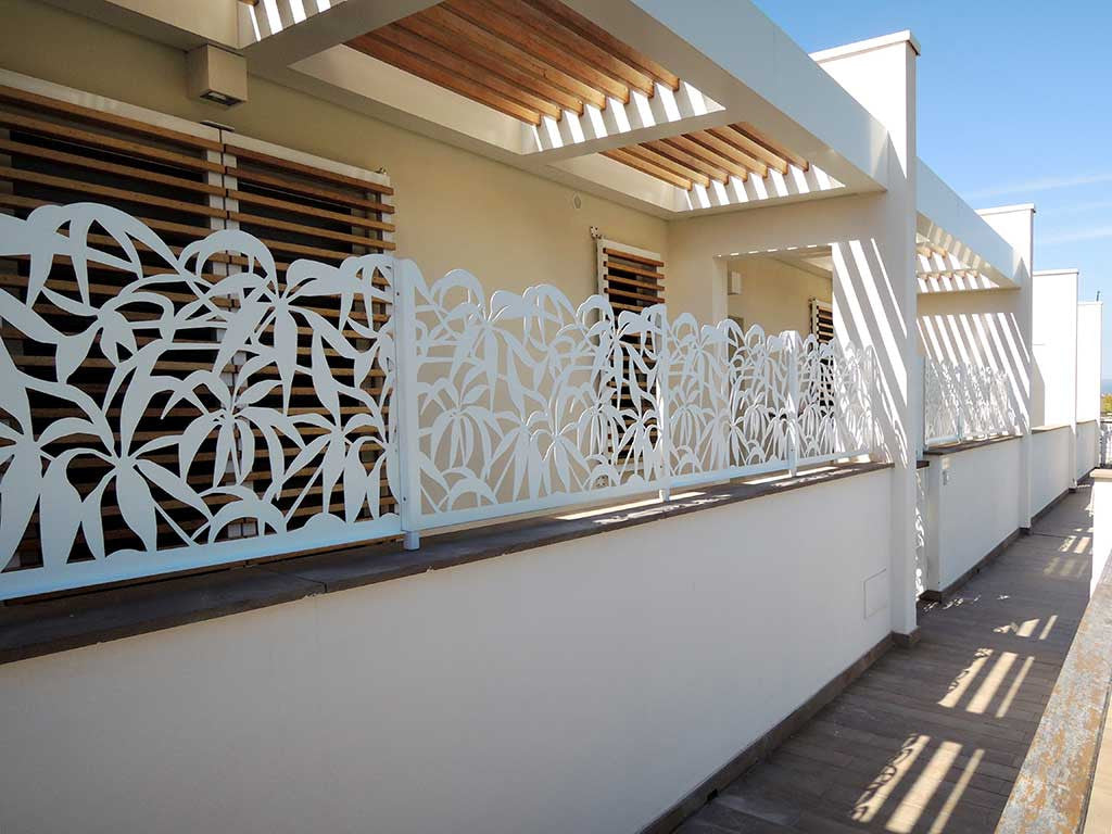 Floral aluminum railing raises the parapet of the marina terrace