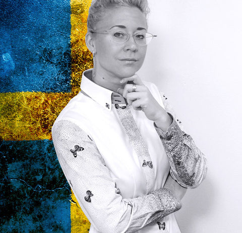 Caroline Wass @Carro, Swedish fashion designer is standing in front of a Swedish flag wearing a white shirt with butterfly details.