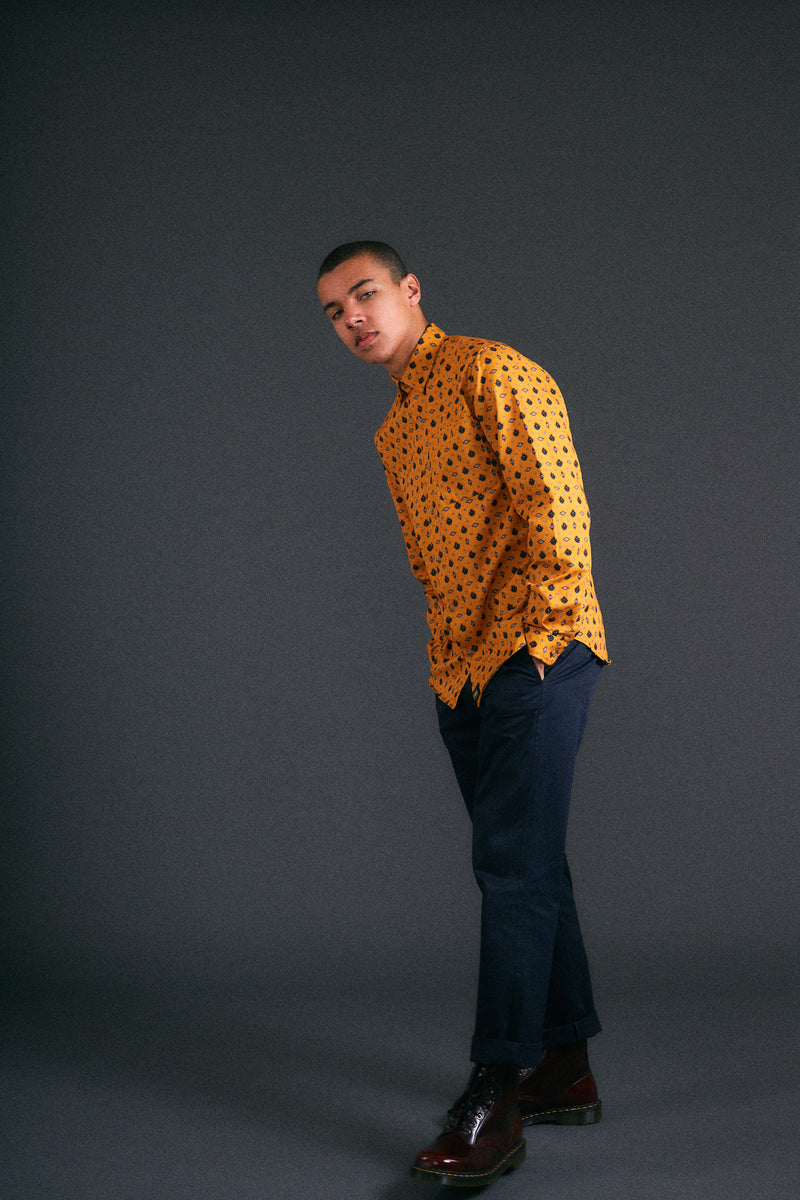 Man wearing a FOMM shirt with floral geometric repetitions on a mustard yellow background.