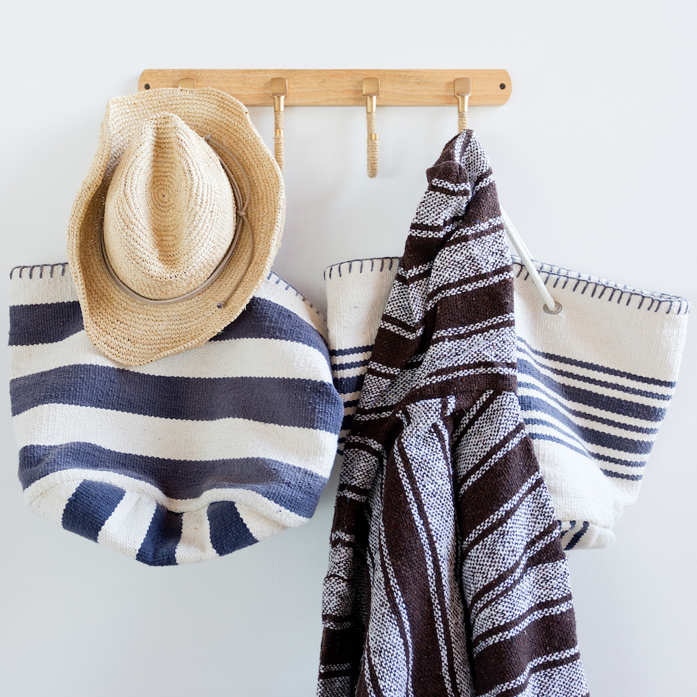 Wall hooks organize blue and white beach bags and hat