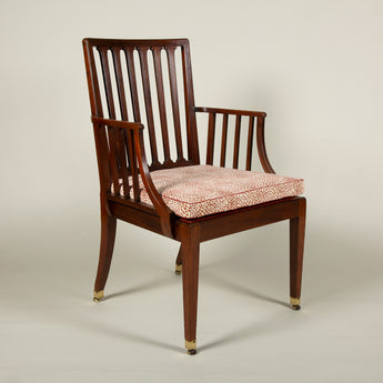 A 19th century mahogany rail back elbow chair now on square tapered legs. With brass and leather roller castors. Circa 1800.