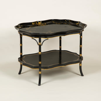 A mid 19th century serpentine papier mache tray with gilt decoration depicting birds and flowers, mounted as a table on a modern faux bamboo stand with a lower tier.