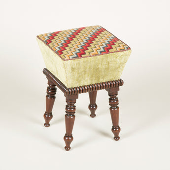 A small early 19th century stool with turned splayed legs and a needlework top.