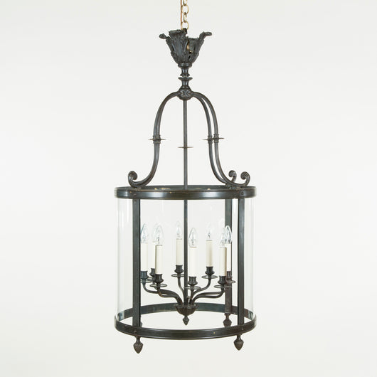 A pair of large early 20th century bronze hall lanterns with scrolled mounts and a scrolled crest.
