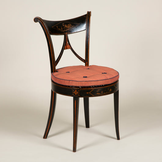 A pair of elegant ebonised side chairs with rounded splayed backs. The top rail painted with rural scenes within a lozenge, and round caned seats. Probably Italian, circa 1810.