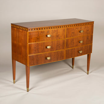 An elegant walnut commode by Paolo Buffa, the gently bowed front with narrow marquetry acanthus leaf frieze over two banks of three drawers with engraved brass handles and tall tapered legs. Milan, 1950's.