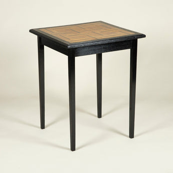 A late 19th or early 20th century square ebonised oak table with a parquetry inlaid top.