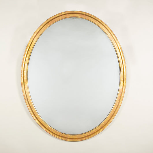 A large oval giltwood mirror with a simple broad frame. 19th century. Original plate, the gilding restored.