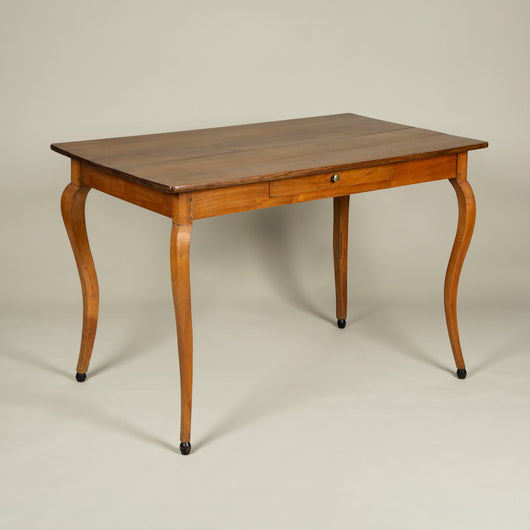 An elegant pear wood desk with one frieze drawer, on slender cabriole legs with ebonised ball feet.
