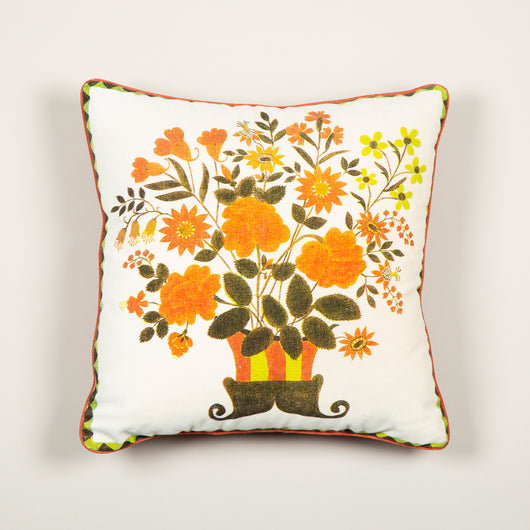 A cushion made up from an archive velvet panel decorated with an image of a tazza of flowers, backed in orange velvet.