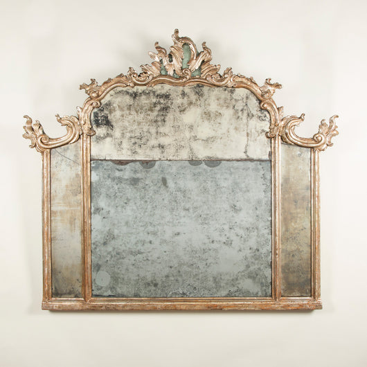 An 18th century Italian Rococo silver-gilt carved wood overmantel mirror with original mirror-plate, circa 1760.