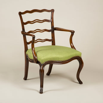 A George III mahogany open armchair with a decorative serpentine ladder back, full upholstered seat and cabriole legs, circa 1770.