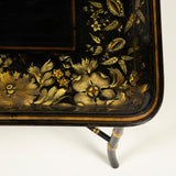A mid 19th century rectangular papier mache tray decorated with a gilt floral border, mounted as a table on a modern faux bamboo stand.