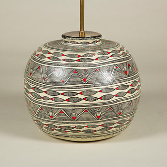 A pot-bellied papier mache pot with red and black geometric decoration on a white ground. Wired as a lamp.