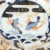 A large Japanese Imari dish, the central reserve decorated with four swimming carp. 18th century.