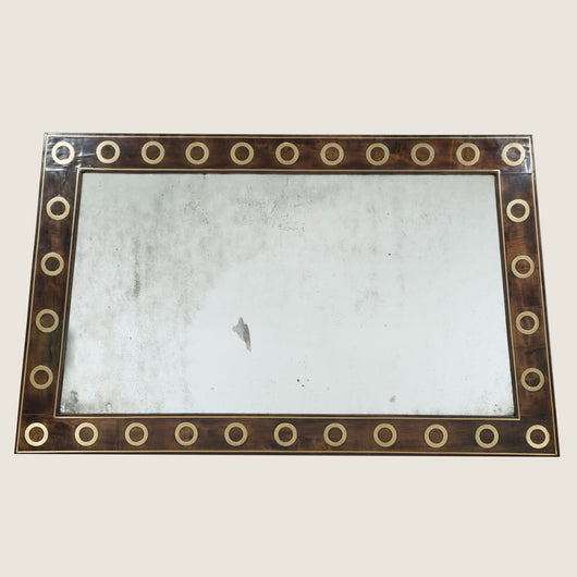 An unusual early 20th century trapezoidal shape mirror with a flat mahogany frame inlaid with circles of brass and brass stringing.