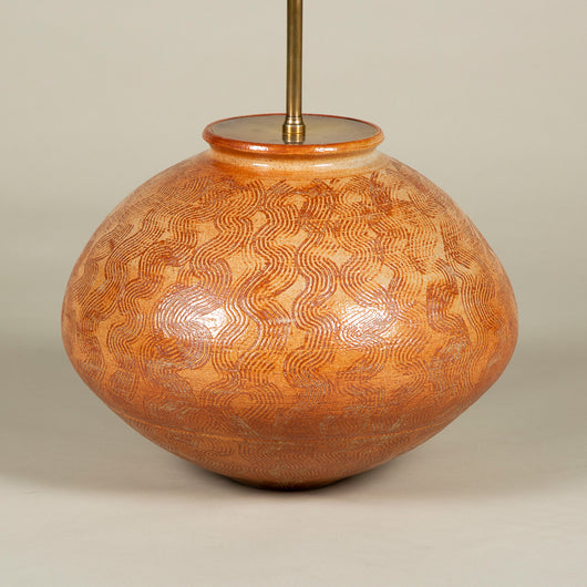 A mid-20th century glazed terracotta art-pottery vase of low form with incised decoration. Wired as a lamp.