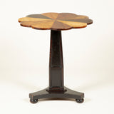 An early 19th century small pedestal table, the round top with petal shaped edges painted to simulate specimens of different woods.