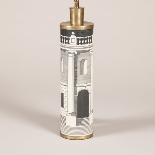 A pair of cylindrical table lamps designed by Fornasetti with architectural decoration and brass mounts, mid-20th century.
