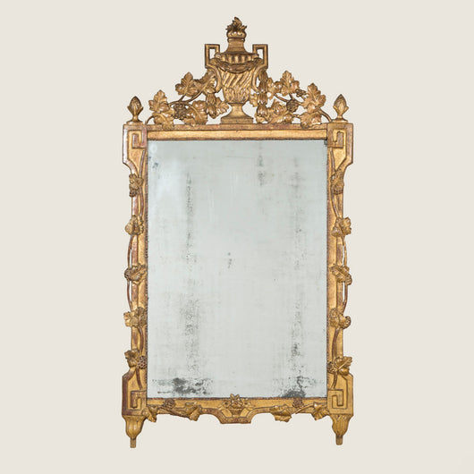 A rectangular Louis XVI giltwood mirror with an urn crest and carved fruiting vine details to the frame. French, circa 1780.